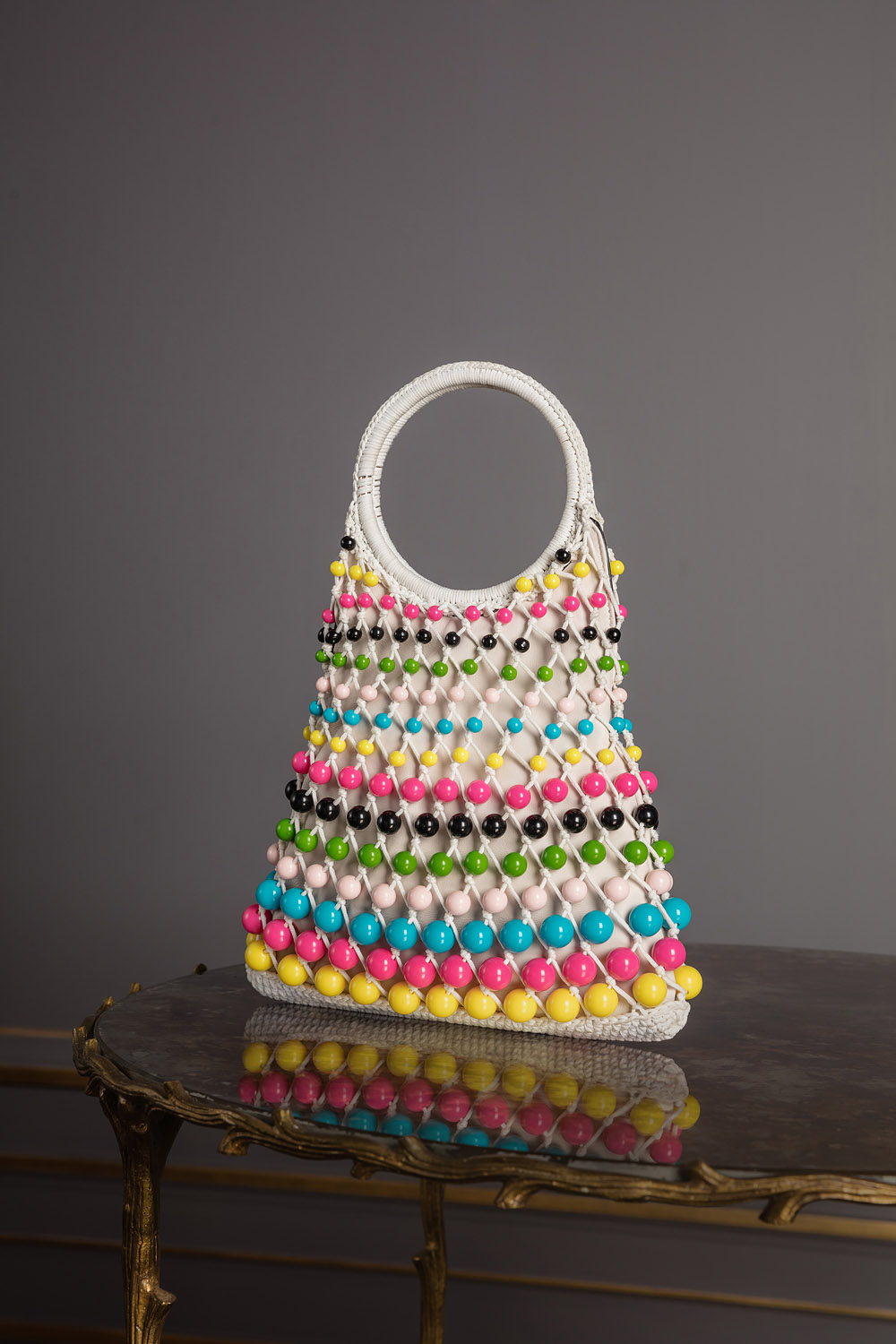 Netted bag decorated with multicolored beads and round handles